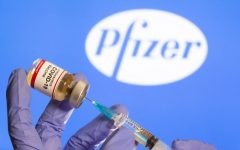 A woman holds a small bottle labeled with a Coronavirus COVID-19 Vaccine sticker and a medical syringe in front of displayed Pfizer logo in this illustration taken, October 30, 2020. REUTERS/Dado Ruvic - RC29TJ9CENFB