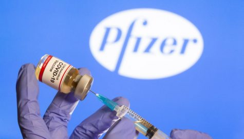 """A woman holds a small bottle labeled with a """"Coronavirus COVID-19 Vaccine"""" sticker and a medical syringe in front of displayed Pfizer logo in this illustration taken, October 30, 2020. REUTERS/Dado Ruvic - RC29TJ9CENFB"""