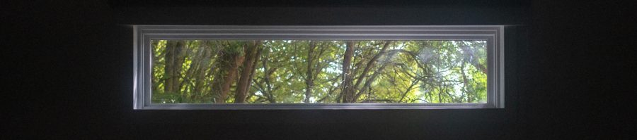 The newly installed window in Kent-Evans, casting a soft, natural light over the overwise dark auditorium.